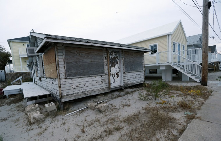"""A boarded bungalow sits beside newly built homes on stilts in the Breezy Point neighborhood Tuesday, Oct. 27, 2015, in New York, before the third anniversary of Superstorm Sandy. Arthur Lighthall, general manager of the Breezy Point Cooperative, said 220 Breezy Point homes were completely destroyed by flooding during Sandy and another 135 homes burned to the ground during a massive fire ignited by the storm. ìEvery day, itís getting a little bit better,î Lighthall said. """"The buildings going up to replace destroyed beach bungalows are being put on high foundations so that future floods will, hopefully, wash beneath the houses rather than bowl them over,"""" he said. (AP Photo/Kathy Willens)"""