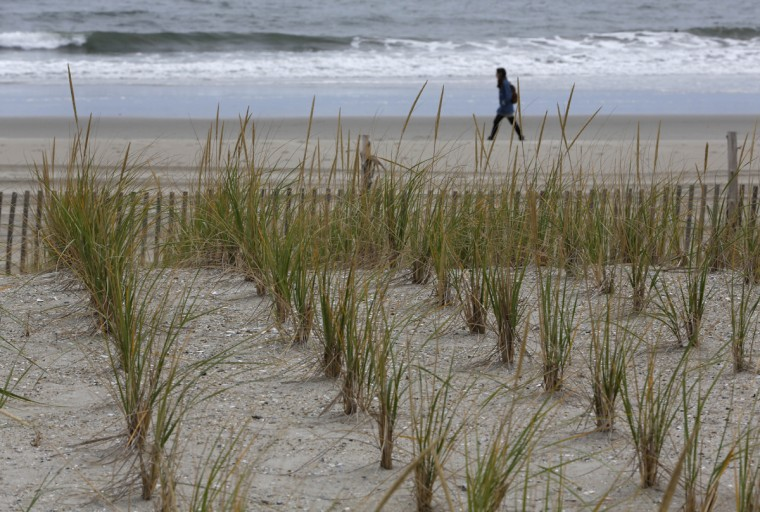Waves roll in as a woman walks along Rockaway Beach before the third anniversary of Superstorm Sandy, Tuesday, Oct. 27, 2015, in New York. To help prevent erosion from rising waters in the environmentally-sensitive area t heavily damaged by Sandy, new sea grasses have been planted . Other improvements include the construction of replacement and new boardwalk sections and additional public facilities. The New York City Department of Parks and Recreation says over $4 million people visited Rockaway Beach last summer. (AP Photo/Kathy Willens)
