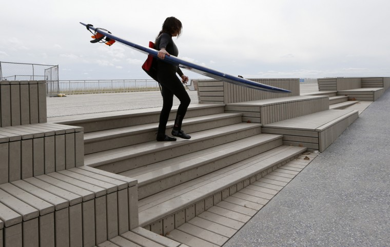 Surfer, photographer and filmmaker Katrina del Mar, who lives near the beach, carries her surfboard down a set of recently constructed steps and benches near Beach 88th Street in the Rockaway Beach section of the Queens borough of New York on Tuesday, Oct. 27, 2015, before the third anniversary of Superstorm Sandy. (AP Photo/Kathy Willens)