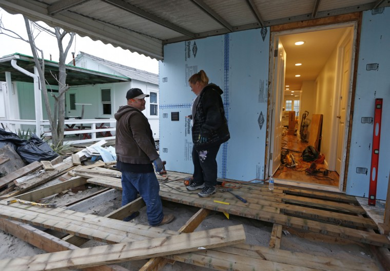 """Habitat for Humanity employees Reynaldo and Anna Acosta hurry to complete the deck of a heavily damaged one-story bungalow owned by a 91-year-old resident in Breezy Point, before the third anniversary of Superstorm Sandy in New York, Tuesday, Oct. 27, 2015. The couple has worked exclusively on rebuilding homes damaged by the storm for nearly the entire three years, initially as volunteers and now as Habitat employees. """"No matter how much work we do,"""" says Anna Acosta, """"there's always more to do."""" According to Breezy Point Cooperative general manager Arthur Lighthall, 220 Breezy Point homes were completely destroyed by flooding during Sandy. (AP Photo/Kathy Willens)"""