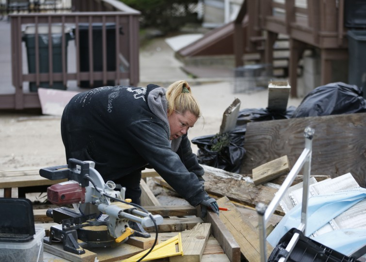 """Habitat for Humanity employee Anna Acosta works on reconstructing the deck of a Breezy Point bungalow before the third anniversary of Superstorm Sandy, Tuesday, Oct. 27, 2015, in New York. Acosta and her husband, Reynaldo, have worked on nearly a dozen Sandy-damaged homes, initially as Habitat volunteers, and now as their full time job. """"No matter how much work we do, there's always more to do,"""" said Acosta. (AP Photo/Kathy Willens)"""