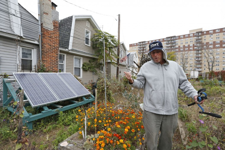"""Retiree Buddy Sammis gestures toward solar panels he and his neighbors used to change their cell phones three years ago after portions of the Rockaway Beach boardwalk washed onto his street severing power lines, as he walks through a neighborhood-run community garden in the Rockaways Tuesday, Oct. 27, 2015, in New York before the third anniversary of Superstorm Sandy. Sammis a longtime surfer, said, """"I miss the (old) boardwalk. It was iconic. It was the longest boardwalk in the world, when it went all the way to 126th Street. Now it's all cement. That's not going to stop anything. If the ocean wants to take the concrete away, it'll happen."""" (AP Photo/Kathy Willens)"""