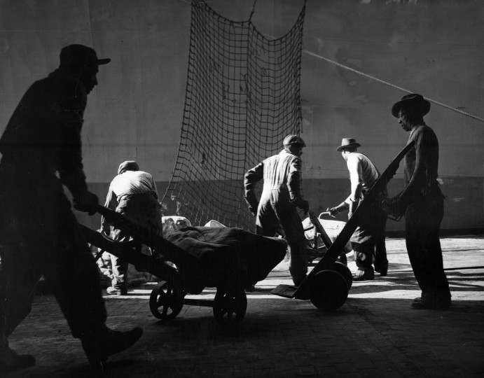 1960 - Longshoremen unload rubber at the B&O Railroad's pier at Locust Point in 1960. It was once a familiar sight to see workers carrying hundred-pound stems of bananas off boats in the harbor. (A. Aubrey Bodine/Baltimore Sun)