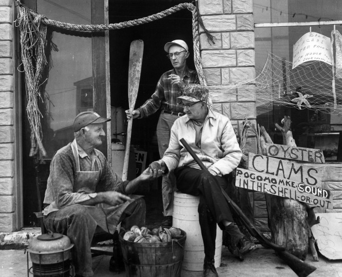 1966 - Down by Crisfield docks, Dewey London opens clams for the Ward brothers. A lifelong friend, London sells souvenirs as well as clams from his store. (A. Aubrey Bodine/Baltimore Sun)