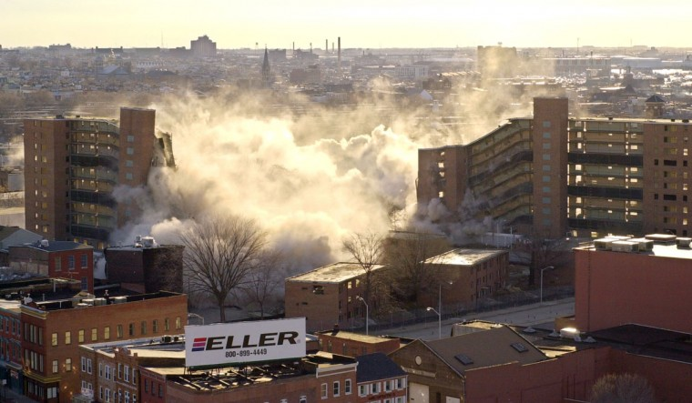 The Flag House Courts high rises come crashing to the ground in about six seconds on Feb. 10, 2001. A stiff breeze from the northwest blows dust towards Little Italy and East Baltimore (in the background). (Baltimore Sun photo by Doug Kapustin)