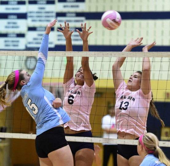 C. Milton Wright's Kira Canter spikes the ball over the net as Bel Air's Lena Sierocinski, left, and Bethany Ingram get up for the block during Monday night's Dig Pink girls volleyball match at Bel Air High School. (Matt Button/BSMG)