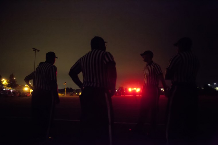 Refs wait on the field after the lights shut off during the third quarter of the Reservoir and Glenelg football game at Reservoir High School in Fulton, MD on Friday, October 9, 2015. (Jen Rynda/BSMG)