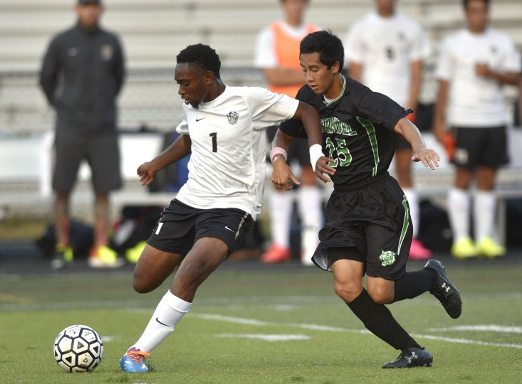Meade's Seth Anokye passes off to a teammate while Arundel's Chris Viado works to take possession during Tuesday nights game at Meade High School. (Matthew Cole/Capital Gazette)