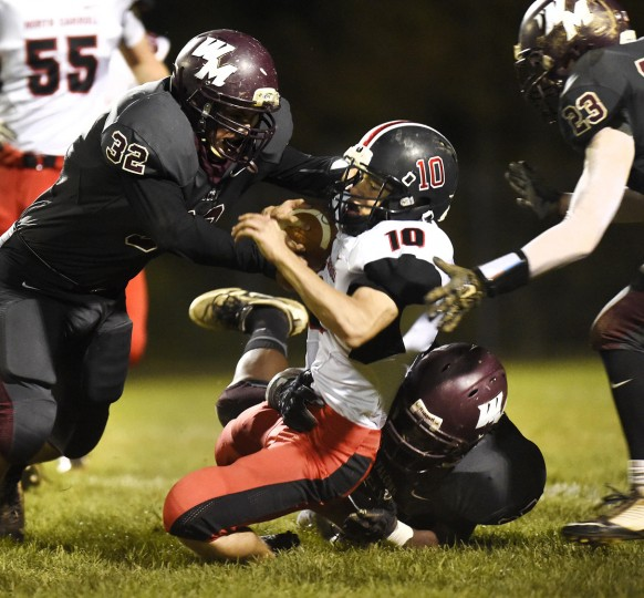 North Carroll's Colton Mott is tackled by Winters Mill's Kyle Sanders during the first half of their game in Westminster Friday, Oct. 16, 2015. (Dylan Slagle/Carroll County Times)