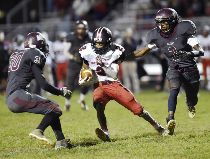 North Carroll's Aaron Nelson carries for a touchdown as Winters Mill's Brady Keller, left, and Dimeon Wright defend, after making a catch in the fourth quarter of the second half of the Panthers' 13-3 win over Winters Mill in Westminster Friday, Oct. 16, 2015. (Dylan Slagle/Carroll County Times)