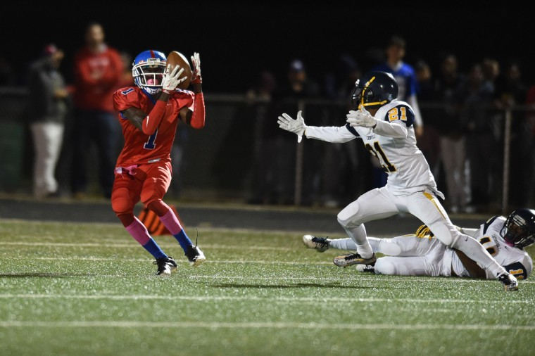 Lansdowne's Kenard Robinson, left, makes a catch on play that first deflected off Catonsville's Zaire Crosby, right, during a football game at Lansdowne High School on Friday, Oct 23. (Brian Krista/BSMG)