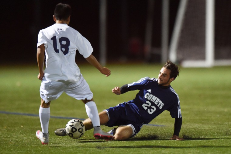 Catonsville'S Matt Rehder makes a sliding stop of the ball in front of Perry Hall's Yejun Kim during the Baltimore County boys soccer championship game at Franklin High School in Reisterstown on Tuesday, Oct 27. (Brian Krista/BSMG)