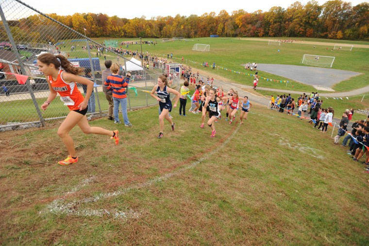Oakland Mills sophomore Grace Shaverini, left, leads a group of competitors up a steep hill in the girls varsity race during the Howard County cross country championships at Centennial High School in Ellicott City on Thursday, Oct 29. (Brian Krista/BSMG)