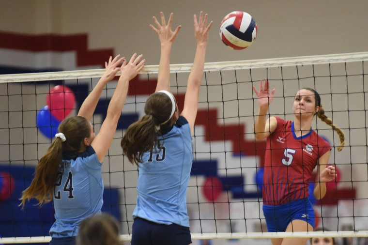 Centennial's Taylor Anderson puts a shot past a pair of Howard blockers during a volleyball match at Centennial High School in Ellicott City on Thursday, Oct 29. (Brian Krista/BSMG)