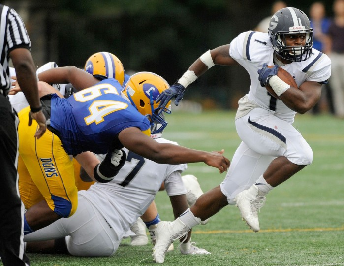 Gilman running back Dorian Maddox, right, breaks away from Loyola defensive lineman Trey Thomas, left, in the second quarter of a high school football game in Towson Friday, Sept. 25, 2015. (Photo by Steve Ruark)
