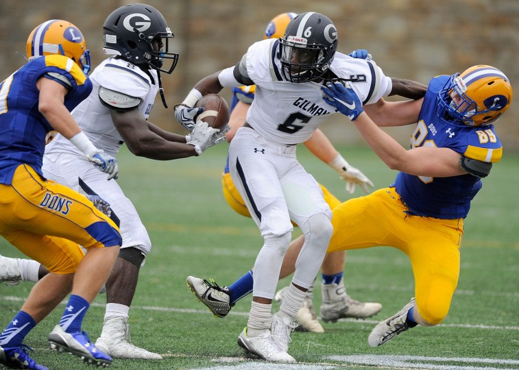 Gilman wide receiver Korey Stevens, third from left, tries to get away from Loyola defensive back Patrick Krack, left, and defensive end Dom Clark, right, as Gilman tight end Shane Lee, second from left, looks to block in the second quarter of a high school football game in Towson Friday, Sept. 25, 2015. (Photo by Steve Ruark)