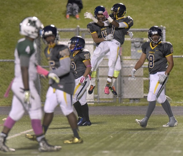Catonsville's Raynard Minter, #4, and Jamal Johnson, #1, celebrate after Johnson returned a punt for a touchdown against Milford Mill in the first half of a high school football game, Thursday, Oct. 15, 2015, in Catonsville. (Steve Ruark/For BSMG)