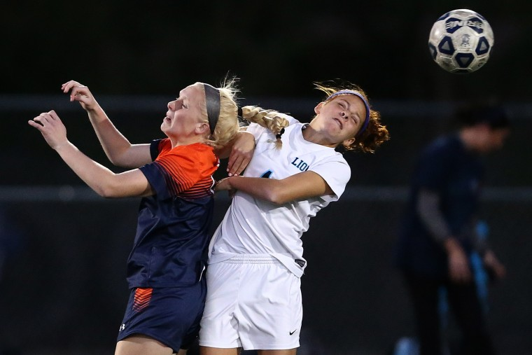 Lauren Maynor, right, of Howard and Kylie Toler of Reservoir go for a header during a soccer match at Howard High School in Ellicott City on Tuesday, October 20, 2015. (Matt Hazlett/For BSMG)