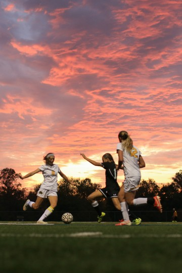 Wilde Lake's #8 Annie Hudec, left, goes for a kick as Atholton's #1 Holly Edsall runs in to block. Atholton Girls Varsity Soccer at Wilde Lake for the county championship, October 22, 2015. (Nate Pesce/For BSMG)