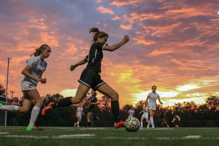 Atholton's #1 Holly Edsall runs with the ball, center, with Wilde Lake's #21 Julianna Bonner behind. Atholton Girls Varsity Soccer at Wilde Lake for the county championship, October 22, 2015. (Nate Pesce/For BSMG)