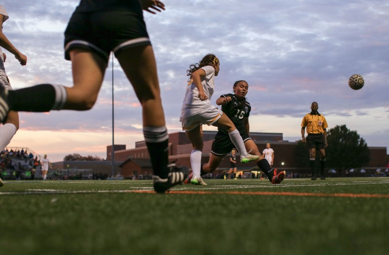 Wilde Lake's #20 Lily Dunbar, center, kicks the ball, as Atholton's #16 Sofia Harrison tries to block it. Atholton Girls Varsity Soccer at Wilde Lake for the county championship, October 22, 2015. (Nate Pesce/For BSMG)