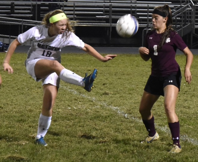 Manchester Valley's Grace Crawford kicks the ball past Winters Mill's Danielle MacDonald. (Ken Koons/Carroll County Times)