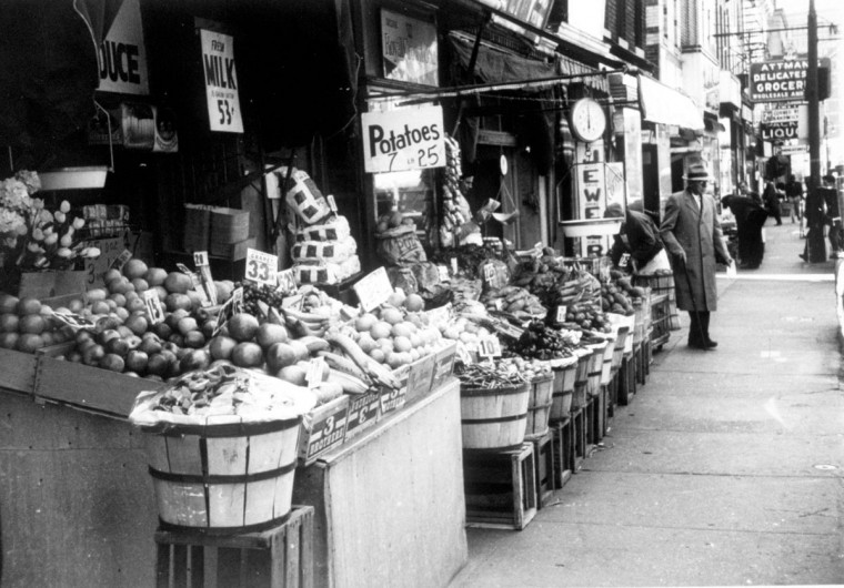 "A view of East Lombard Street in 1963, when food stores in the street's glory days included Wartzman's bakery, Smelkinson's dairy, Pastore's fruits and vegetables, Tulkoff's horseradish, Yankeloff's chickens, Attman's deli, Holzman's bakery, Spivak's chickens, Gottlieb's dairy, and Stone's bakery. In the spring of 1967, following the assassination of the Reverend Martin Luther King, Jr., many of these buildings gave way to empty lots. (Photo from the Sandler book: ""Jewish Baltimore: A Family Album."")"