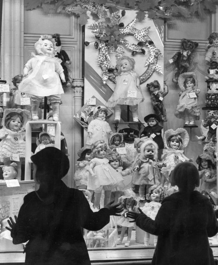 1938 - Not even the hard times of the Great Depression could kill the dreams of children. Here, two young girls, take in a display of dolls in a downtown department store. (A. Aubrey Bodine/Baltimore Sun)