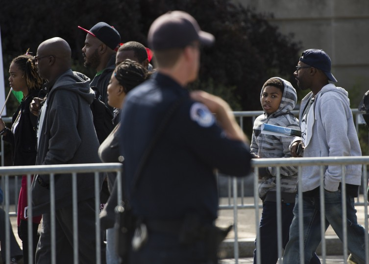 A young boy looks at a police officer as he enters the Justice or Else! rally on the National Mall in Washington, DC on October 10, 2015. The rally commemorates the 20th anniversary of the Million Man March which took place on October 16, 1995. (Andrew Caballero-Reynolds/AFP-Getty Images)