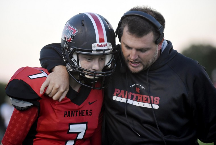 North Carroll head coach Todd Edmondson congratulates quarterback Cooper Hastings after he scored a touchdown against Brunswick during the first half of their game in Hampstead Monday, Oct. 5, 2015. (Dylan Slagle/Carroll County Times)
