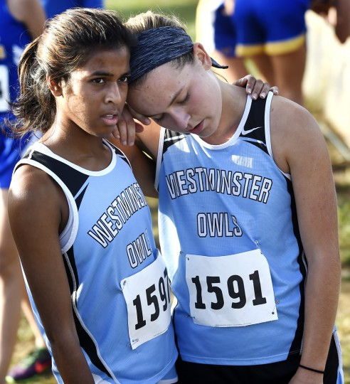 Westminster junior Chandra Reiff, left, and senior Kamilla Haldorsen rest after finishing the girls race in the Crossfire Invitational cross country meet at Liberty High School in Eldersburg Tuesday, October 6, 2015. (Dylan Slagle/Carroll County Times)