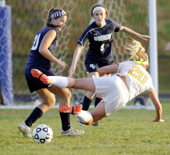 Century's Hannah Warther goes down on an approach to the goa as Manchester Valley's Sami Chenowith and Kelsey Henneman defend during the first half of their game in Eldersburg Monday, Oct. 26, 2015. (Dylan Slagle/Carroll County Times)