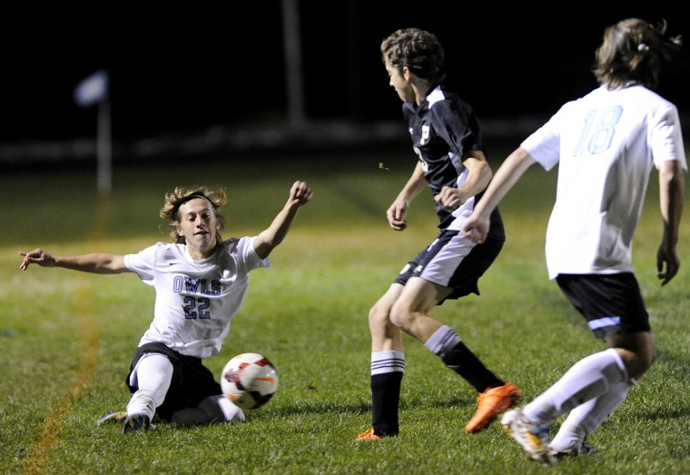 Westminster's Ryan Walsh keeps the ball in bounds with a slide in front of Poolesville's Logan Saar Thursday, Oct. 29 in Westminster. (Dave Munch/Carroll County Times)