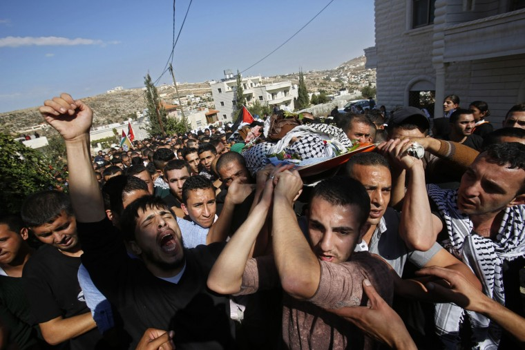 Palestinian mourners carry the body of 22 year-old, Raed Jaradat, during his funeral in the West Bank village of Sa'ir, near Hebron, Sunday, Nov 1, 2015. According to the Israeli army Jaradat stabbed an Israeli before being shot and killed. In recent days, Hebron has become a main flashpoint of Israeli-Palestinian violence, with near-daily deadly confrontations at Israeli checkpoints that guard ultra-nationalist Jewish settlers in the center of the city. (AP Photo/Nasser Shiyoukhi)