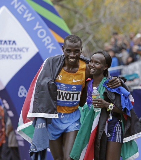 Kenya's Stanley Biwott, left, embraces fellow Kenyan Mary Keitany after the pair won the men's and women's professional women's athlete divisions in the the New York City marathon, Sunday, Nov. 1, 2015 in New York. (AP Photo/Kathy Willens)