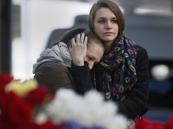 Young women grieve at an entrance of Pulkovo airport outside St.Petersburg, Russia, on Monday, Nov. 2, 2015. In a massive outpouring of grief, thousands of people flocked to St. Petersburg's airport, laying flowers, soft toys and paper planes next to the pictures of the victims of the crash of a passenger jet in Egypt that killed all 224 on board in Russia's deadliest air crash to date. (AP Photo/Dmitry Lovetsky)