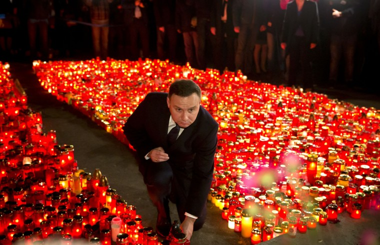 Polish President Andrzej Duda places a candle outside the Colectiv nightclub, in Bucharest, Romania, Monday, Nov. 2, 2015. The owners of the Colectiv nightclub were questioned by prosecutors Monday in connection with a fire that engulfed a nightclub Friday night, causing a stampede to a single exit door of the basement club and leaving tens of people dead and many more injured. (AP Photo/Vadim Ghirda)