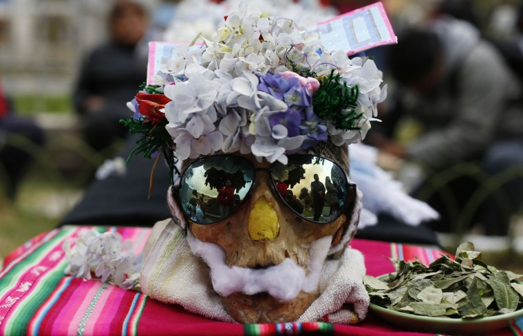"A human skull or ""natitas"" wearing sun glasses and crowned with flowers is surrounded by offerings of coca leaves, flower petals and cigarettes, outside the Cementerio General chapel during the Natitas Festival, in La Paz, Bolivia, Sunday, Nov. 8, 2015. Although some natitas have been handed down through generations, many are from unnamed, abandoned graves that are cared for and decorated by faithful. They use them as amulets believing they serve as protection. The tradition marks the end of the Catholic All Saints holiday, but is not recognized by the Catholic church. (AP Photo/Juan Karita)"
