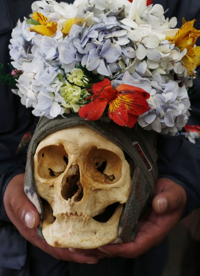 "A woman carries decorated human skull or ""natitas"", as she waits to be greeted by the priest inside the Cementerio General chapel, during the Natitas Festival celebrations, in La Paz, Bolivia, Sunday, Nov. 8, 2015. Although some natitas have been handed down through generations, many are from unnamed, abandoned graves that are cared for and decorated by faithful. They use them as amulets believing they serve as protection. The tradition marks the end of the Catholic All Saints holiday, but is not recognized by the Catholic church. (AP Photo/Juan Karita)"