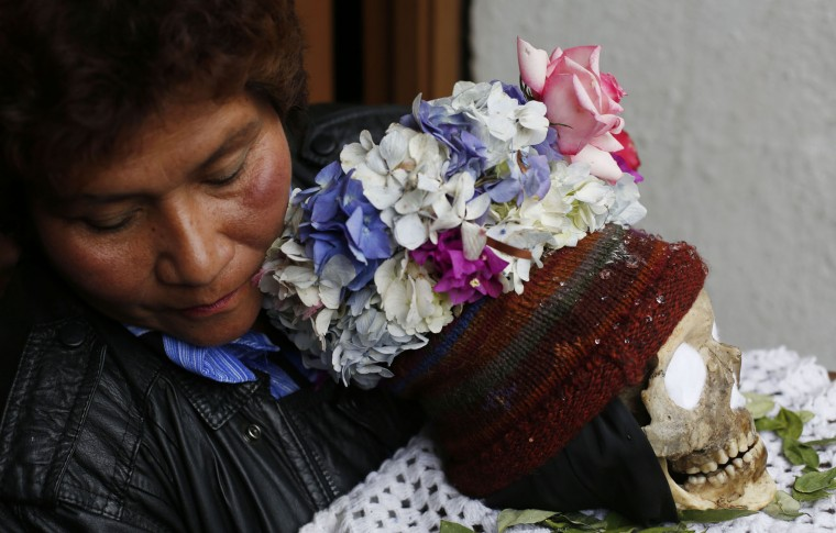"A woman carries a decorated human skull or ""natitas"" outside the Cementerio General chapel, during the Natitas Festival celebrations, in La Paz, Bolivia, Sunday, Nov. 8, 2015. Although some natitas have been handed down through generations, many are from unnamed, abandoned graves that are cared for and decorated by faithful who use them as amulets believing they serve as protection. The tradition marks the end of the Catholic All Saints holiday, but is not recognized by the Catholic church. (AP Photo/Juan Karita)"