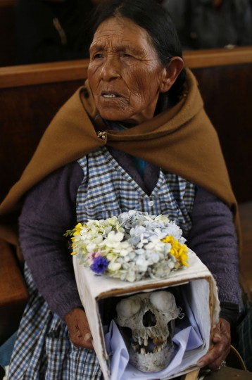 "A woman holds decorated a human skull or ""natitas"" as she waits to be greeted by the priest inside the Cementerio General chapel, during the Natitas Festival celebrations, in La Paz, Bolivia, Sunday, Nov. 8, 2015. Although some natitas have been handed down through generations, many are from unnamed, abandoned graves that are cared for and decorated by faithful who use them as amulets believing they serve as protection. The tradition marks the end of the Catholic All Saints holiday, but is not recognized by the Catholic church. (AP Photo/Juan Karita)"