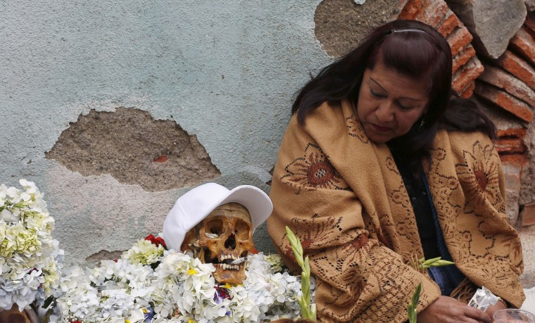 "A woman looks at her decorated human skull or ""natitas"" as she waits to be greeted by the priest inside the Cementerio General chapel, during the Natitas Festival celebrations, in La Paz, Bolivia, Sunday, Nov. 8, 2015. Although some natitas have been handed down through generations, many are from unnamed, abandoned graves that are cared for and decorated by faithful who use them as amulets believing they serve as protection. The tradition marks the end of the Catholic All Saints holiday, but is not recognized by the Catholic church. (AP Photo/Juan Karita)"