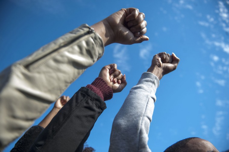 Protesters raise their fists to celebrate Tim Wolfe's resignation during the Concerned Students 1950 protest on Monday, Nov. 9 2015, in Columbia, Mo. (Michael Cali/San Diego Union-Tribune/TNS)