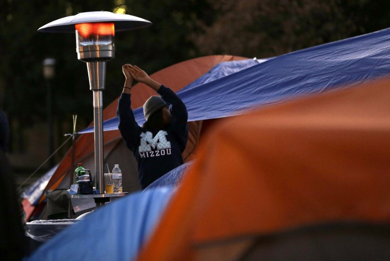 A student protester warms her hands under a heater as dusk falls on a tent encampment set up Monday, Nov. 9, 2015, on the campus of the University of Missouri in Columbia, Mo. The president of the University of Missouri System and the head of its flagship campus resigned Monday with the football team and others on campus in open revolt over what they saw as indifference to racial tensions at the school. (AP Photo/Jeff Roberson)