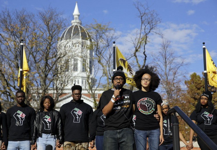 Jonathan Butler, front left, addresses a crowd following the announcement that University of Missouri System President Tim Wolfe would resign Monday, Nov. 9, 2015, at the university in Columbia, Mo. Butler has ended his hunger strike as a result of the resignation. (AP Photo/Jeff Roberson)