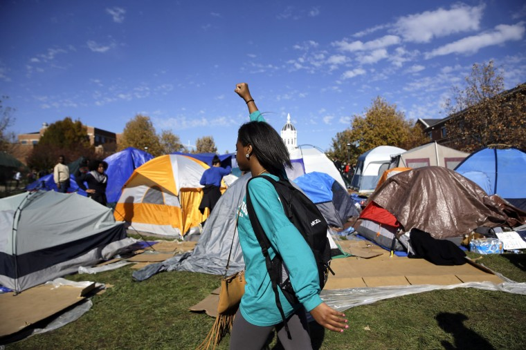 A woman passes a tent encampment set up by student protesters following an announcement that University of Missouri System President Tim Wolfe is resigning Monday, Nov. 9, 2015, at the university in Columbia, Mo. Wolfe resigned Monday with the football team and others on campus in open revolt over his handling of racial tensions at the school. (AP Photo/Jeff Roberson)