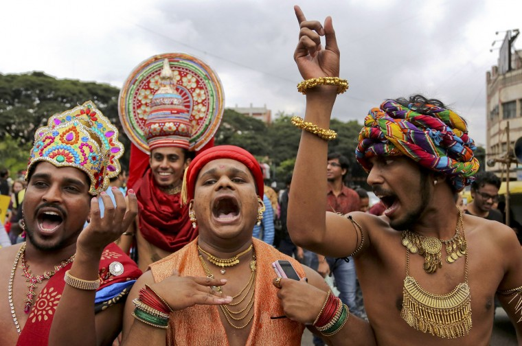 Members and supporters of lesbian, gay, bisexual and transgender community, in traditional attire shout slogans during 'Pride March' rally in Bangalore, India, Sunday, Nov. 22, 2015. Gay rights supporters waved flags and danced past traffic during the march to celebrate gay pride and to push for the repeal of a colonial-era law that makes homosexuality a crime. (AP Photo/Aijaz Rahi)