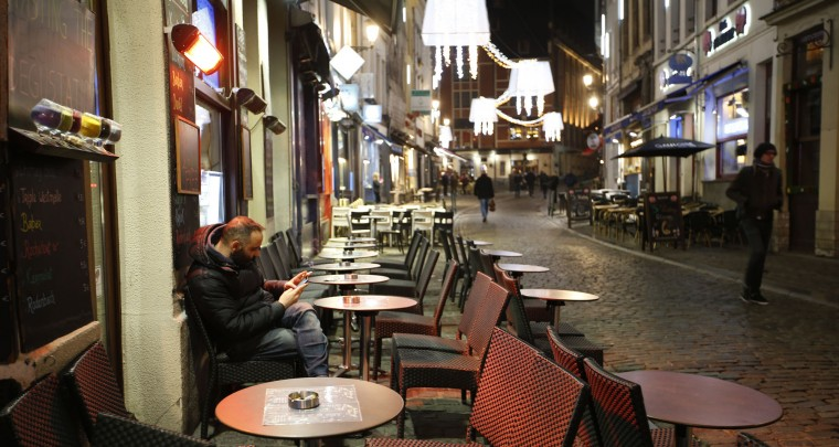A man smokes a cigarette and looks at his smartphone under a heating lamp, in what would normally be a busy tourist area of central Brussels, Monday, Nov. 23, 2015. The Belgian capital Brussels has entered its third day of lockdown, with schools and underground transport shut and more than 1,000 security personnel deployed across the country. (AP Photo/Alastair Grant)