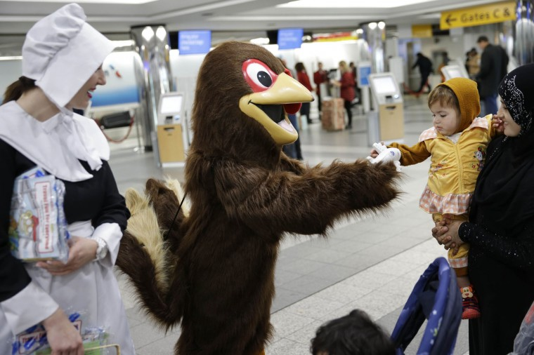 A person in a turkey costume gives Nasreen Qasimi, 1, a toy airplane at LaGuardia Airport in New York, Tuesday, Nov. 24, 2015. (AP Photo/Seth Wenig)