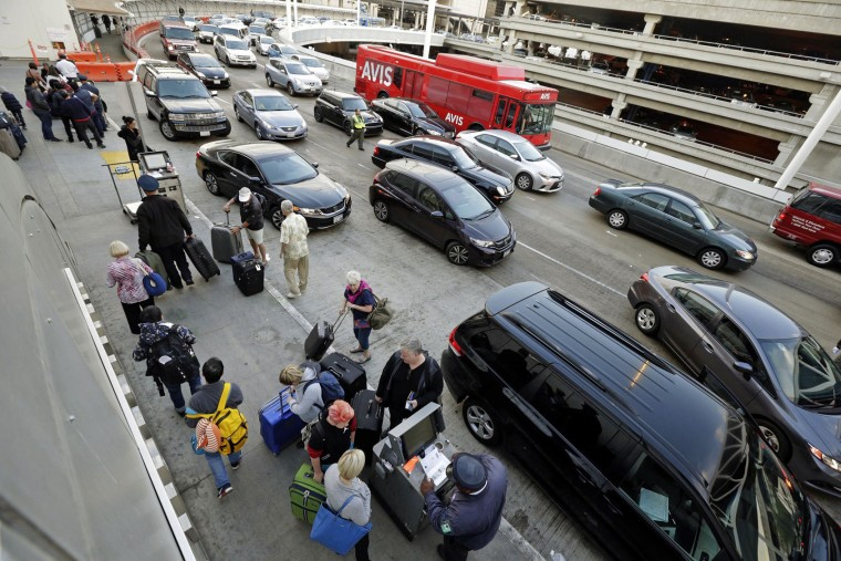 Holiday travelers appear at Los Angeles International Airport, on Tuesday, Nov. 24, 2015. An estimated 46.9 million Americans are expected to take a car, plane, bus or train at least 50 miles from home over the long holiday weekend, according to the motoring organization AAA. (AP Photo/Nick Ut)